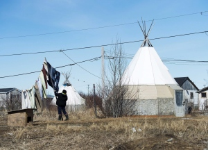 An indigenous women takes down laundry in the northern Ontario First Nations reserve in Attawapiskat, Ont., on April 19, 2016. (THE CANADIAN PRESS / Nathan Denette)