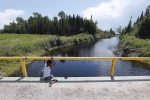 A boy from the Shoal Lake 40 First Nation sits on a bridge over a channel on on June 25, 2015. (John Woods / The Canadian Press)
