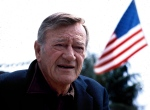 """This 1978 file photo shows actor John Wayne. Wearing a brown plaid coat worn by Wayne in 1945's """"Flame of Barbary Coast,"""" Republican Lt. Gov.  (AP Photo)"""