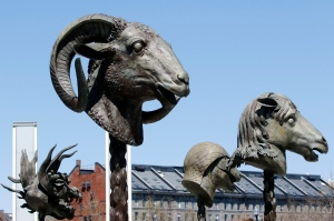 In this Wednesday, April 27, 2016 photo, four of 12 gigantic bronze animal heads representing the signs of the zodiac by Chinese artist Ai Weiwei stand in a circle on the Rose Kennedy Greenway in Boston. Lucas Cowan, the public art curator of the Greenway Conservancy, says they are replicas of smaller sculptures stolen from an imperial Chinese palace in 1860. The sculptures are scheduled to remain on public display in the park through October. (AP Photo/Bill Sikes)