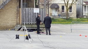 Investigators look through evidence at the scene of an overnight shooting on John Street downtown on Friday, April 29, 2016. (Justin Zadorsky / CTV London)