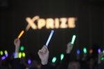 Visioneering 2014 attendees hold up glowsticks at an XPRIZE presentation. (XPRIZE)