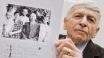 Auschwitz survivor Max Eisen shows a photograph from 1940 that shows him, centre, with his parents and brothers, Thursday, April 23, 2015, in a courtroom in Lueneburg, northern Germany.  (Julian Stratenschulte/Pool via AP)