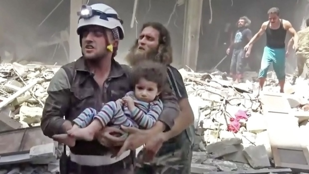 In this image made from video and posted online from Validated UGC, a Civil Defense worker carries a child after airstrikes hit Aleppo, Syria, Thursday, April 28, 2016. (Validated UGC via AP video)