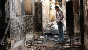 In this Oct. 16, 2015, file photo, an employee of Doctors Without Borders walks inside the charred remains of the organization's hospital after it was hit by a U.S. airstrike in Kunduz, Afghanistan. (AP Photo / Najim Rahim, File)