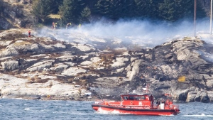 A search and rescue vessel patrols off the coast of the island of Turoey, near Bergen, Norway, as emergency workers attend the scene after a helicopter crashed believed to be have 13 people aboard, Friday, April 29, 2016. (Rune Nielsen / NTB scanpix via AP)