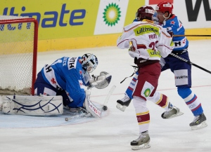 Prague's Daniel Pribyl, centre, fights for the puck with St. Petersburg's goalkeeper Jakub Stepanek and Sergei Gusev, right back, during the game between SKA St. (AP Photo/Keystone, Arno Balzarini)