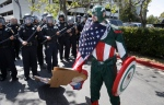 Erik Lopez of Hercules dressed as 'Captain Mexico' joins protesters gathered outside the Hyatt Regency Hotel where Republican Presidential candidate Donald Trump kicked off the California Republican Party Convention in Burlingame, Calif., Friday, April 29, 2016. (Michael Macor / San Francisco Chronicle via AP)
