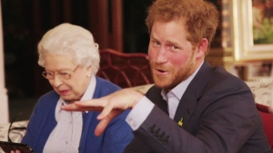 This image taken from a video released by Kensington Palace, London, on Friday April 29, 2016 shows Queen Elizabeth II sitting with her grandson, Prince Harry as he says 'Boom' whilst receiving a video call from the President of the United States, Barack Obama and Michelle Obama.(@KENSINGTONROYAL via AP)