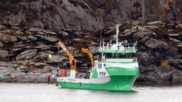 A recovery vessel lifts up parts of a crashed helicopter from off the island of Turoey, near Bergen, Norway, as emergency workers on the shoreline attend the scene Friday, April 29, 2016.  (Vidar Ruud/NTB scanpix via AP)