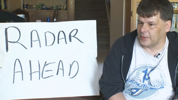 """Jack Shultz sits next to his """"radar ahead"""" sign during an interview with CTV Edmonton."""