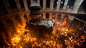 Christian Orthodox pilgrims hold candles during the Holy Fire ceremony in the church of the Holy Sepulchre, traditionally believed to be the burial site of Jesus Christ, Saturday, April 30, 2016 in Jerusalem.  (AP /Dusan Vranic)