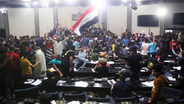 Supporters of Shiite cleric Muqtada al-Sadr storm parliament in Baghdad's Green Zone, Saturday, April 30, 2016. Dozens of protesters climbed over the blast walls and could be seen storming the Parliament building, carrying Iraqi flags and chanting against the government. (AP Photo/ K halid Mohammed)