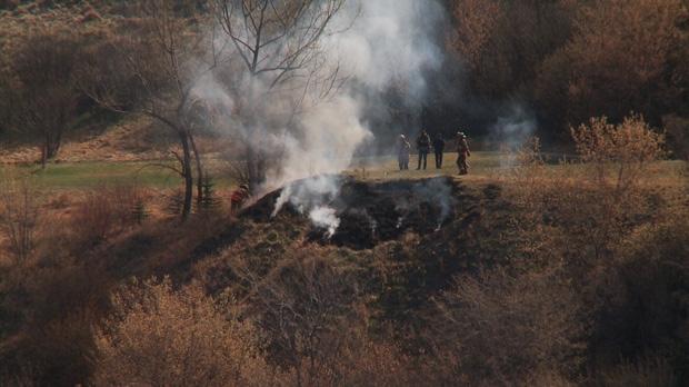 Fire crews battle grass fires on riverbank