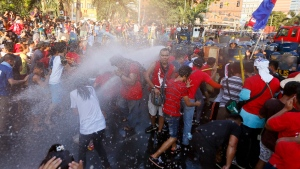Protesters, mostly workers, are dispersed with water cannon as they try to force their way closer to the gates of the U.S. Embassy in Manila to mark the International Labor Day Sunday, May 1, 2016 in Manila, Philippines. (AP Photo/Bullit Marquez)