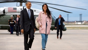 President Barack Obama jokes with his daughter Malia Obama as they walk to board Air Force One from the Marine One helicopter Thursday, April 7, 2016, as they leave Chicago en route to Los Angeles. (AP Photo/Jacquelyn Martin)