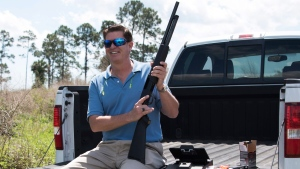 """In this photo taken April 7, 2016, Jonathan Mossberg, whose iGun Technology Corp. is working to develop a """"smart gun,"""" poses with the firearm, in Daytona Beach, Fla. (AP Photo/Lisa Marie Pane)"""
