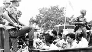 In this Oct. 30, 1965 photo, members of the Youth Wing of the Indonesian Communist Party (Pemuda Rakjat) are guarded by soldiers as they are taken by open truck to prison in Jakarta.   (AP Photo)