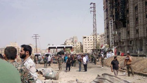 Gathering at the scene of a suicide attack at a military checkpoint at the entrance to the Sayyida Zeinab suburb, Damascus, on April 25, 2016. (SANA via AP)