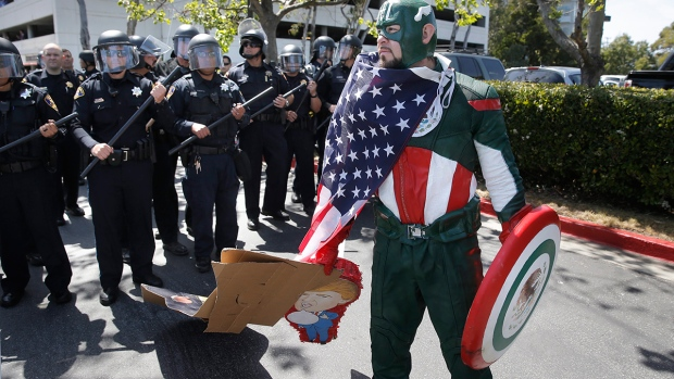 Erik Lopez of Hercules dressed as 'Captain Mexico' joins protesters gathered outside the Hyatt Regency Hotel where Republican Presidential candidate Donald Trump kicked off the California Republican Party Convention in Burlingame, Calif., Friday, April 29, 2016. (Michael / San Francisco Chronicle via AP).