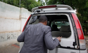 Abdiqadir Dulyar, director for the Somali television station Horn Cable, looks at the smashed window of a car that was carrying journalists working for his station, that unidentified gunmen opened fire on last week although no one was hurt, in Mogadishu, Somalia Tuesday, May 3, 2016.  (AP / Farah Abdi Warsameh)