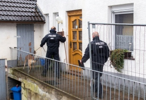 A member of the German police with a dog stands in front of the house of a murder suspect couple in Hoexter, Germany, Tuesday, May 3, 2016. (Marcel Kusch / dpa)