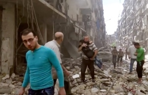 In this Thursday, April 28, 2016 image made from video and posted online from Validated UGC, a man carries a child after airstrikes hit Aleppo, Syria. (Validated UGC via AP video)