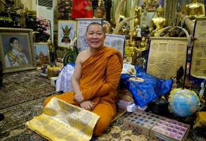 Chief monk at the Wat Traimitr Withayaram temple Phra Prommangkalachan smiles as he addresses the media in a room with Leicester City memorabilia and a portrait of Thai King Bhumibol Adulyadej, left, in Bangkok, Thailand, Tuesday, May 3, 2016. (AP / Mark Baker)