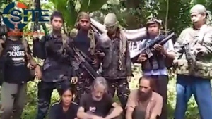 Philippine militants claiming to belong to Abu Sayyaf are seen holding hostages, from left to right, Filipina Marites Flor, Canadian Robert Hall, and Norwegian Kjartan Sekkingstad, in a still frame made from a militant video accessed by the U.S.-based SITE Intelligence Group. (HO-SITE Intelligence Group/The Canadian Press)