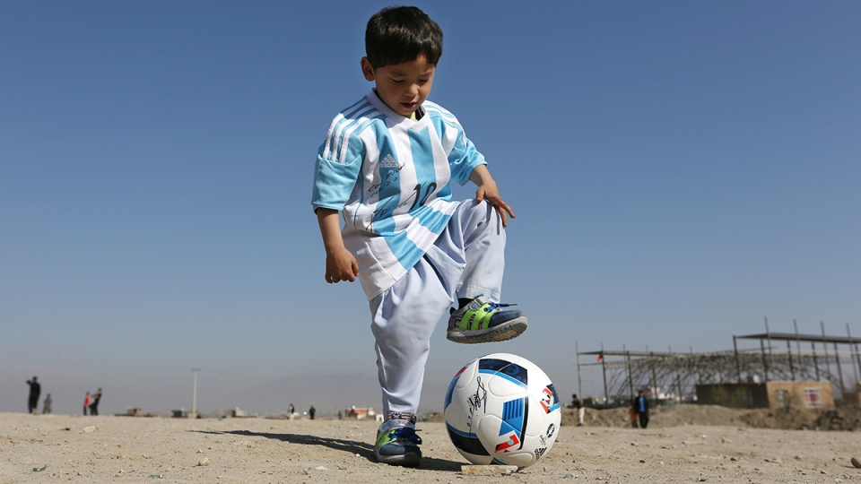 Murtaza Ahmadi, a five-year-old Afghan Lionel Messi fan plays with a soccer ball during a photo opportunity as he wears a shirt signed by Messi, in Kabul, Afghanistan, Friday, Feb. 26, 2016. (AP / Rahmat Gul)