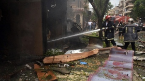 Syrian citizens and firefighters gather at the scene where one of rockets hit the Dubeet hospital in the central neighborhood of Muhafaza in Aleppo, Syria, Tuesday, May 3, 2016. (SANA via AP)