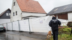 A police officer with a dog passes by a house outside Hoexter, western Germany, Tuesday, May 3, 2016. (Marcel Kusch / dpa via AP)