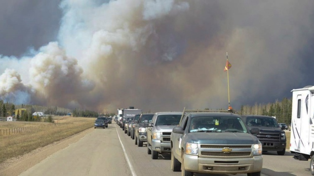 Smoke fills the air as people drive on a road in Fort McMurray, Alta. on Tuesday May 3, 2016. (Greg Halinda / THE CANADIAN PRESS)