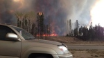 Smoke fills the air and trees burn in Fort McMurray, Alberta on Tuesday May 3, 2016. (Kitty Cochrane / THE CANADIAN PRESS)