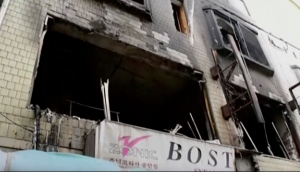 In this May 2, 2016 image, made from video provided by DVIDS, a building is burned after a fire where residents, including U.S. servicemen, used a blanket to catch a woman and her three children as they jumped to safety in Pyeongtaek, South Korea. (DVIDS via AP)