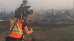 A CTV News camera operator surveys the devastation after officials said 80 per cent of homes have been lost to wildfires in Beacon Hill, Alta., on Wednesday, May 4, 2016. (Breanna Karstens-Smith / CTV News)
