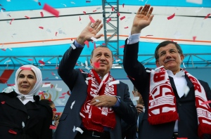 In this April 22, 2016 file photo, Turkey's President Recep Tayyip Erdogan, center, and Prime Minister Ahmet Davutoglu, right, salute together during a ceremony in Antalya,  (Yasmin Bulbul, Presidential Press Service)