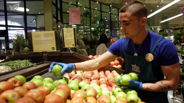 FILE - In this Nov. 3, 2010 file photo, a man stocks apples in the produce section at Whole Foods, in Coral Gables, Fla. (AP Photo/Lynne Sladky)