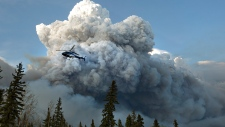 A helicopter flies past wildfire in Fort McMurray