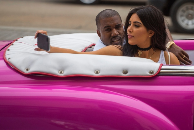 American reality-show star Kim Kardashian takes a selfie as she rides on a classic car next to her husband, rap singer Kanye West in Havana, Cuba, Wednesday, May 4, 2016. West, Kardashian and members of her reality-show-star family have become the latest celebrities to visit Havana. They visited Havana's Museum of Rum Wednesday, stepping out of a hot-pink antique American convertible as they snapped selfies and were recorded by a television crew following them around.(AP Photo/Desmond Boylan)