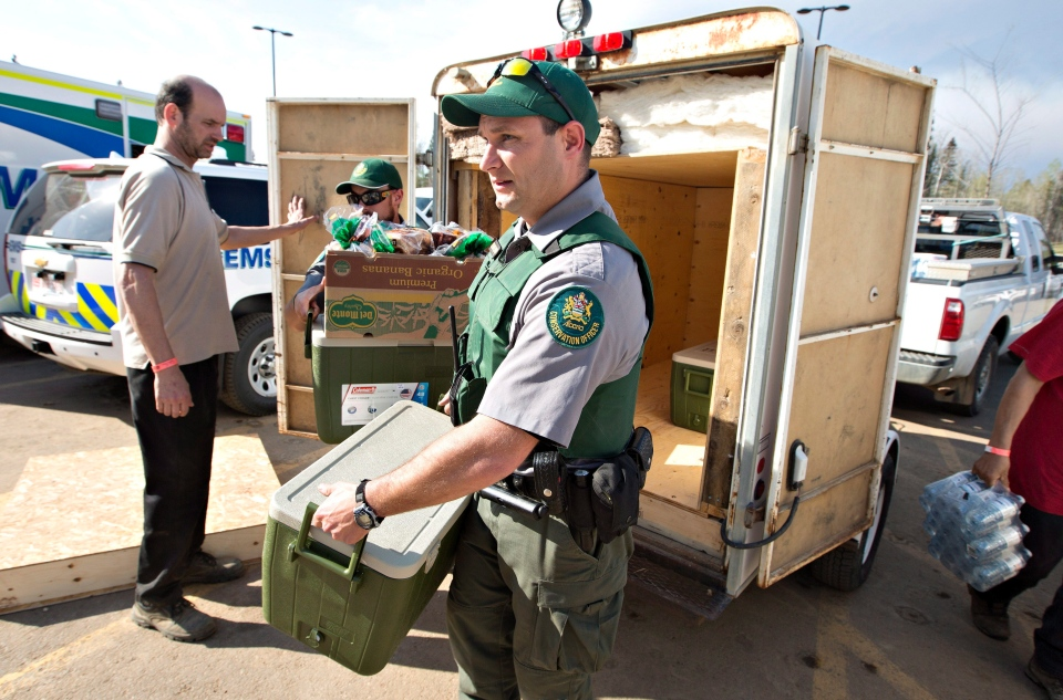 Conservation officers haul supplies to the Evacuation Centre in Anzac south of Fort McMurray, Alta., on Wednesday May 4, 2016. (THE CANADIAN PRESS / Jason Franson)