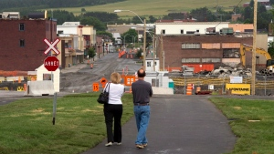 A couple looks at the downtown core Friday, July 4, 2014 in Lac-Megantic, Que. (Ryan Remiorz / THE CANADIAN PRESS)