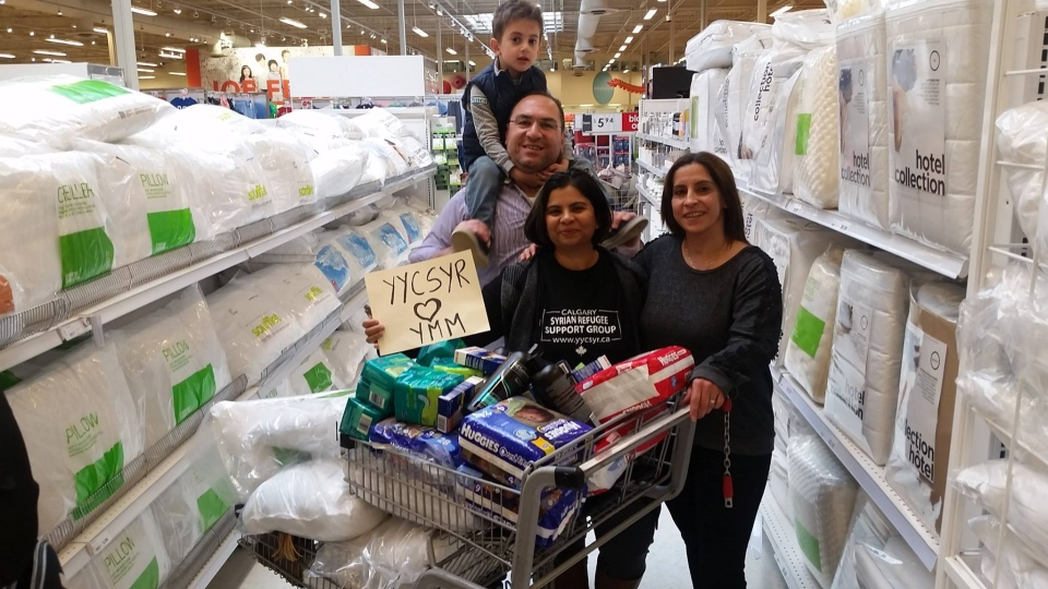 Saima Jamal (centre), the co-founder of the Calgary-based Syrian Refugee Support Group, is seen buying donations to help residents of Fort McMurray with Syrian refugee Rita Khanchat and her husband Salen (left) and son Eli (top left). (Syrian Refugees Support Group Canada)