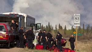 Fire Rescue crews unload in preparation to battle a wildfire in Fort McMurray, Alta., on Thursday, May 5, 2016. (Jason Franson / THE CANADIAN PRESS)