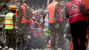 Rescuers gesture to their colleagues as they try to free a woman who was trapped for six days in the rubble of a collapsed building, in the Huruma area of Nairobi, Kenya, Thursday, May 5, 2016. (AP / Ben Curtis)