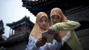 Two Chinese Hui Muslim girls read the Quran, Islam's holy book, at the Niujie Mosque as they wait for their fast on the first day of the Muslim holy month of Ramadan in Beijing on Aug. 1, 2011. (AP / Andy Wong)