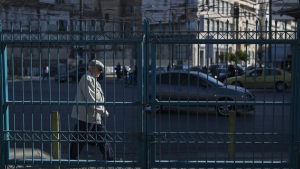 A man walks behind a locked passengers' entrance of Athens' port of Piraeus which is on strike, on Friday, May 6, 2016. (AP / Petros Giannakouris)