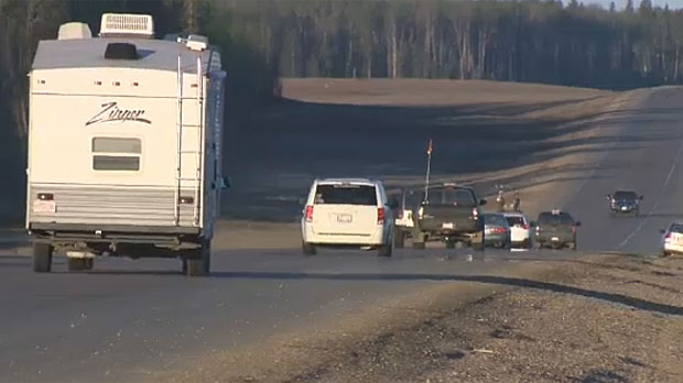 RCMP are escorting vehicles out of work camps north of Fort McMurray on Friday. About 25,000 people fled there after a mandatory evacuation order was called on Tuesday.
