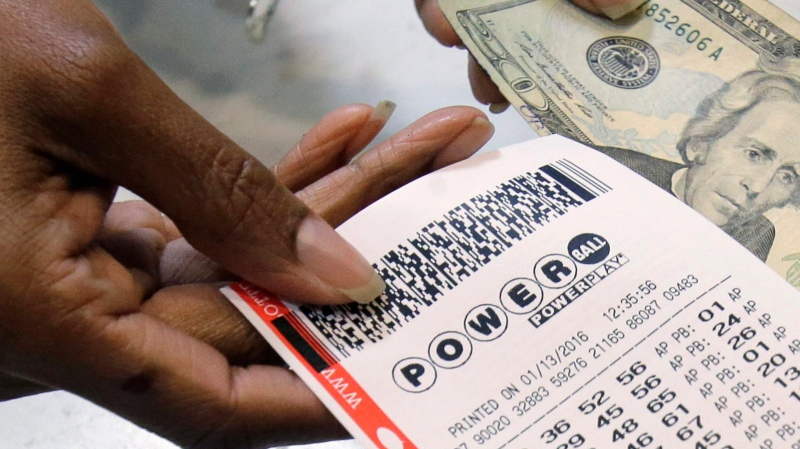 In this Jan. 13, 2016 file photo, a clerk hands over a Powerball ticket for cash at Tower City Lottery Stop in Cleveland. (AP Photo/Tony Dejak)