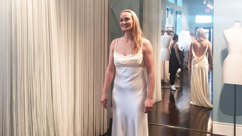 Élise Boissonneult tries on a new wedding dress at Lea-Ann Belter Bridal in Toronto. Her original dress was destroyed in the Fort McMurray wildfire. (Alex Neary / Wild Eyed Photography)